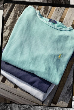 Folded pile of terry sweatshirts in mint, navy & white