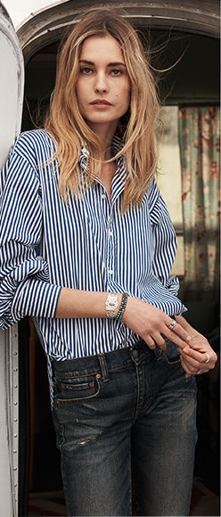 Model in blue-and-white striped button-down & dark-wash jeans