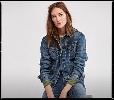 Model in medium-wash denim trucker jacket