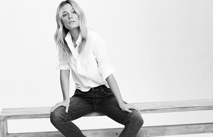 Model in classic white button-down tucked into jeans