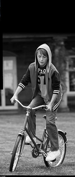 Black-and-white image of boy riding bike in jeans and hoodie.