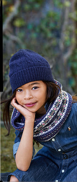 Girl wears denim shirtdress, navy knit beanie, and patterned scarf.