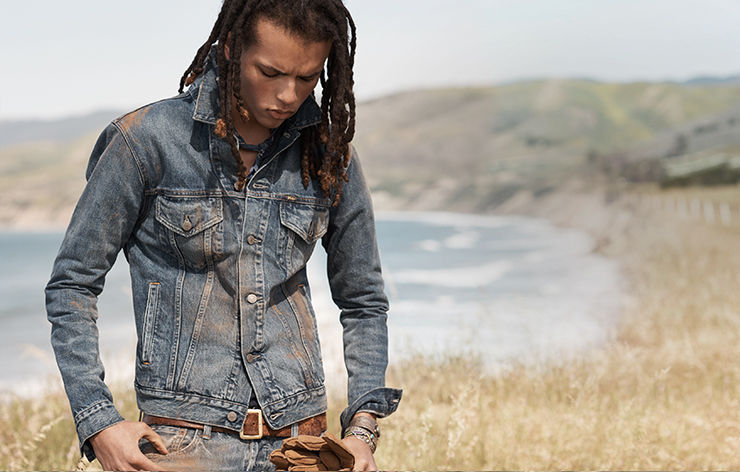 Model in worn denim jacket, jeans & brown leather belt