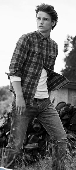 Model wears plaid shirt over white tee, paired with ripped jeans