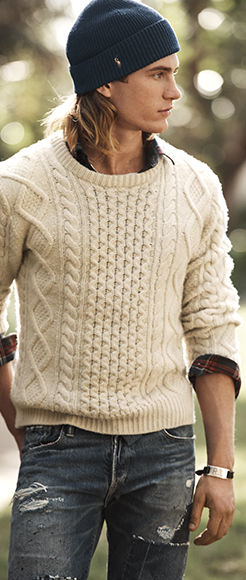 Model in multi-patterned cream sweater, navy knit hat & distressed jeans