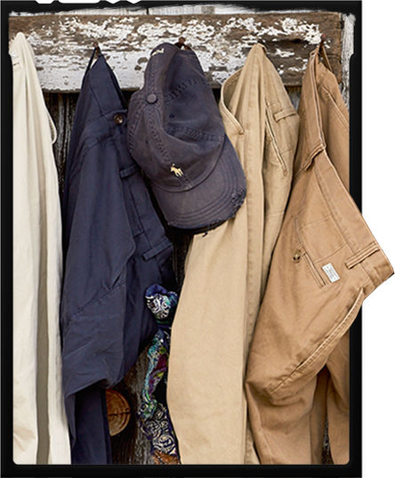 Chinos of various shades, from tan to navy, hang from hooks