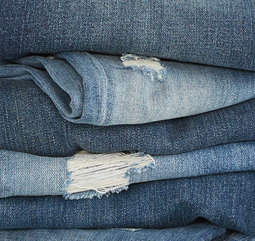 Stack of folded jeans in different shades with distressing