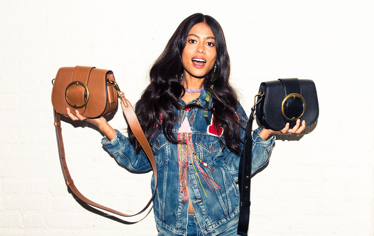 Arpana Rayamajhi holds up handbags from the Ralph Lauren Lennox collection