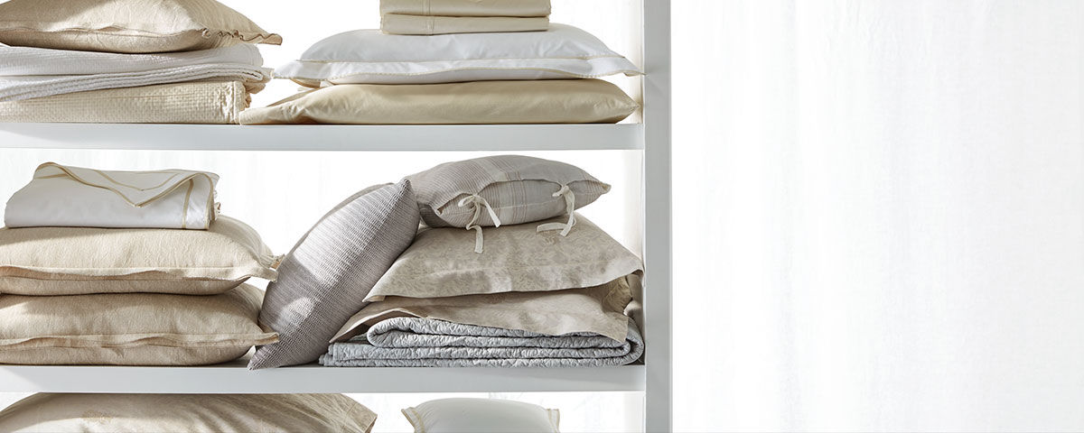 Shelves piled with ivory-toned Lauren Home pillows & sheeting