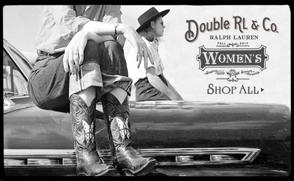 Two women sit on hood of car in cowboy boots & hats