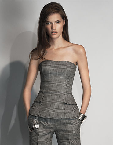 Woman in plaid peplum bustier with sweetheart neckline & flapped pockets