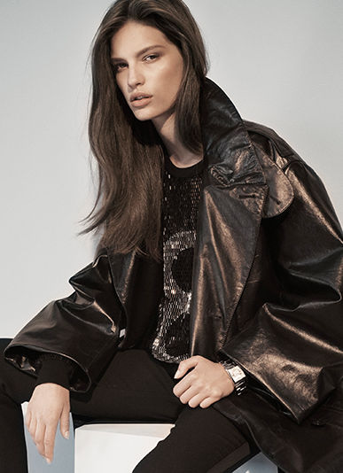 Model wears black sweater with large metallic 8 at front