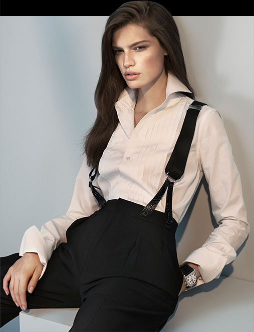 Model in pleated-front whit shirt worn with suspendered pants