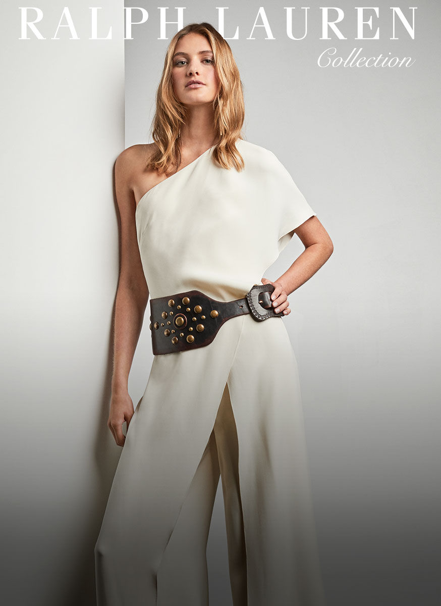 Woman anchors cream-colored one-shoulder jumpsuit with wide studded leather belt
