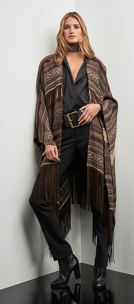 Woman layers striped, fringed poncho over black blouse, pant & leather belt