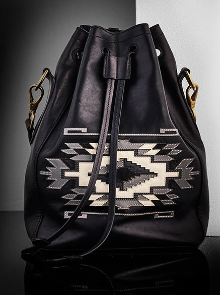 Black leather Ricky Drawstring Bag with Southwestern-inspired design in contrasting tones