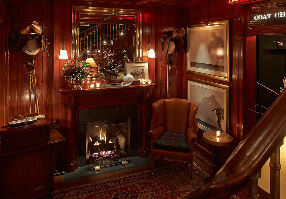 Lounge area at The Polo Bar with lit fireplace.