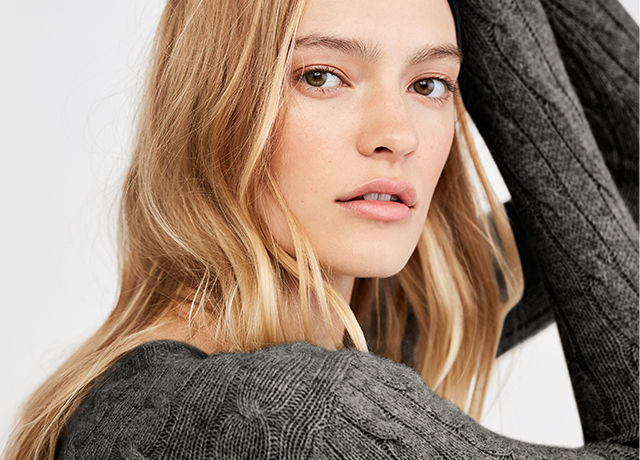 Close-up image of model in light grey cable-knit sweater