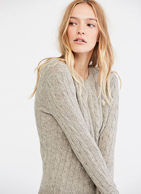 Model in light grey cable sweater with arms crossed