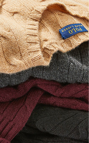 Close-up image of stacked cable sweaters in autumn hue
