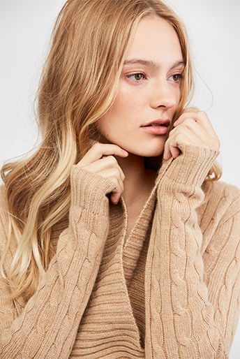Closed-up image of model in camel-hued shawl-collar sweater