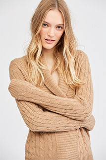 Model with arms crossed in camel cable sweater